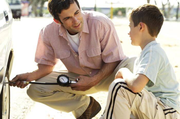 Young Man Checking the Air Pressure of Car Tire with His Son --- Image by © Royalty-Free/Corbis